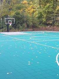 One end of large basketball court in Bolton, MA, also lined for pickleball with a rollable portable net.