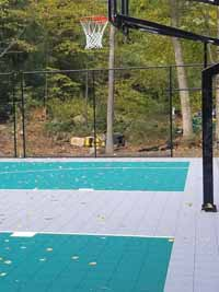 Fixed basketball goal at one end of a large multi-purpose basketball court in Bolton, MA.