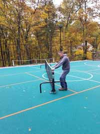 Demonstrating deployment of portable yet durable net system to center of large basketball multicourt in Bolton, MA. Court was ordered with lined for pickleball. Portable nets roll easily then lock down, giving option of net sports like tennis on demand without permanent posts or nets.