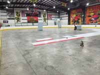 We traveled to Kapolei, Hawaii and inside to resurface two inline skate hockey rinks with Versacourt Speed Indoor tile. This is a look at just over half of the court, with installation begun at the center line, and pallets of material staged beyond.