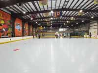 We traveled to Kapolei, Hawaii and inside to resurface two inline skate hockey rinks with Versacourt Speed Indoor tile. This is a long view of a large expanse of tiled but unlined court, with work still in progress at the far end.