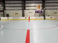 We traveled to Kapolei, Hawaii and inside to resurface two inline skate hockey rinks with Versacourt Speed Indoor tile. This is near the center of the completed hockey court, showing the faceoff circle in the neutral zone.
