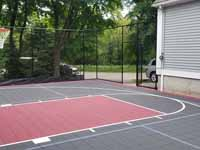 Milton, MA basketball court in a side yard, fit flush against a garage, featuring red and graphite Versacourt tiles.