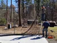 Residential basketball court in Norwell, MA, including goal system, mesh fencing, and an emerald green and rust red tile sport surface. Some trees and stumps were removed to make room in the yard and provide easy work access. This shows workers installing net fencing onto previously installed posts.