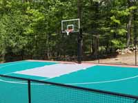 Residential backyard basketball court on fresh concrete base in stalled in Pepperell, MA, featuring fencing and an emerald green, titanium, and rust red sport tile surface.