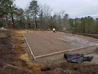 Hillside court primarily for pickleball, accessorized with a basketball goal and fencing, in Plymouth, MA. This shows the nearly completed form and rebar reinforcement for cement to be poured for the court foundation.