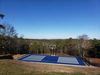 Hillside court primarily for pickleball, accessorized with a basketball goal and fencing, in Plymouth, MA.
