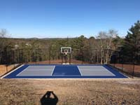 Multicourt for pickleball and basketball, fenced on three sides, on a hillside backyard in Plymouth, MA. Straight on image of completed court and scenic view down the hill beyond.