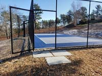 Multicourt for pickleball and basketball, fenced on three sides, on a hillside backyard in Plymouth, MA.