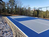 Multicourt for pickleball and basketball, fenced on three sides, on a hillside backyard in Plymouth, MA. Finished blue and grey court from open long side, at an angle, in late fall sun.
