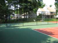 Restoration and resurfacing of large tennis court into multicourt with hopscotch and shuffleboard for a condo complex in Duxbury, Massachusetts. Shuffleboard area separated by containment fence.