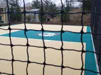 Photo from installation of a sand and emerald green residential backyard basketball court in Swampscott, MA.