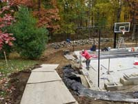 Graphite and titanium residential backyard basketball court in Westford, MA, with retaining wall, gated containment fence, and wood rail fence. Shown here during construction.