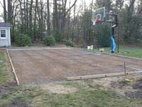 Form with rebard for pouring reinforced concrete base, shown with hoop already installed, for green and grey backyard basketball court installation in Agawam, MA.