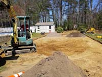 Excavation and fill work precursor to green and grey backyard basketball court installation in Agawam, MA.
