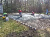 Cement work in construction of the base for a dark green and grey backyard basketball court in Agawam, MA.