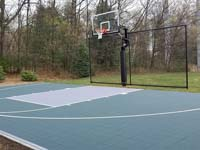 Dark green and grey backyard basketball court with hoop and rebounder in Agawam, MA.