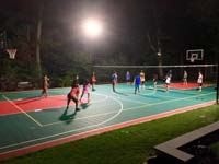 Large multicourt in use under the lights at night for a game of volleyball in Pembroke, MA.