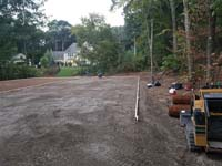 Packing gravel underlay and the forms and reinforcement for concrete partially in place on the way to building a large emerald green and titanium backyard basketball court in Bolton, MA.