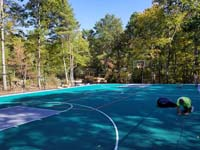 Installation largely complete of ergonomic, low-impact tiles that form the final surface of a large emerald green and titanium backyard basketball court in Bolton, MA.