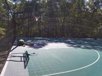 Sunny view of part of large emerald green and titanium backyard basketball court in Bolton, MA, with workers doing some final construction details.