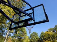 Skyview from beneath hoop at one end of large emerald green and titanium backyard basketball court in Bolton, MA.