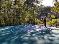 Closer view of one end of large emerald green and titanium backyard basketball court in Bolton, MA, showing off hoop system and containment fence.