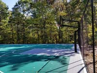 Side view of most of hoop and key end of large emerald green and titanium backyard basketball court in Bolton, MA.