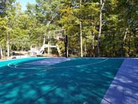 View of one end of large emerald green and titanium backyard basketball court in Bolton, MA.