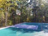 Focus on end zone, showing off fence and goal, of large emerald green and titanium backyard basketball court in Bolton, MA.