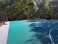 View of much of large emerald green and titanium backyard basketball court in Bolton, MA with tiles still being installed along one side.
