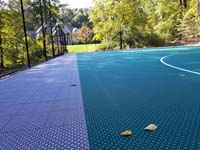 Relatively close view of Versacourt tile that makes up the surface of large emerald green and titanium backyard basketball court in Bolton, MA, looking down much of the length of one side, along the containment fence.