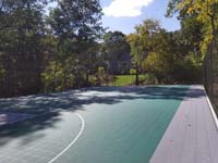 Sun-drenched long view of most of large emerald green and titanium backyard basketball court in Bolton, MA.