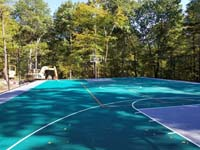 Long view of most of large emerald green and titanium backyard basketball court in Bolton, MA.