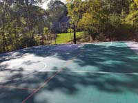 View of one end of large emerald green and titanium backyard basketball court in Bolton, MA, mottled with sun and tree shadows.