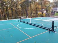 Portable pickleball net in place at center of pickleball lines on large emerald green and titanium backyard basketball court in Bolton, MA.