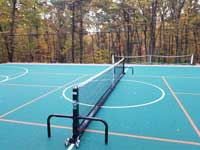 Commercial sized green residential basketball court in Bolton, MA features multiuse orange lines for pickleball, using a portable net shown here.