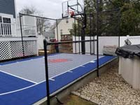 Small blue and grey basketball court by pool in Braintree, MA.