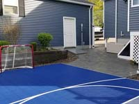 View of entry corner of blue and grey basketball court in Braintree, MA, showing hockey net and associated patio.