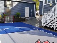 View from hoop end of small blue and grey basketball court with custom red H logo in Braintree, MA, showing customer's hockey net and patio they had installed to go with court.