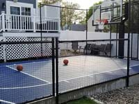 Blue and grey basketball court in Braintree, MA, after finishing landscape and hardscape touches around it were completed.
