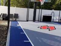 Closeup of blue and grey basketball court surface with custom H logo in Braintree, MA, after finishing landscape and hardscape touches around it were completed.
