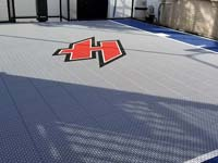 Closeup detail of custom red H logo on small blue and grey basketball court in Braintree, MA.