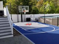 Small blue and grey basketball court with custom red H logo by existing pool in Braintree, MA, shown after completion of associated hardscapes.