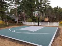 Dark green basketball court in Duxbury, MA, waiting for owner's finishing landscape touches to make it even better.