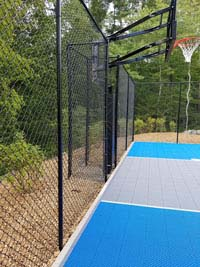 Blue and gray residential basketball court in Easton, MA, viewed from back side, highlighting fence and goal.