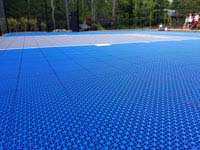 Closeup of Versacourt tile surface of blue and gray residential basketball court in Easton, MA.