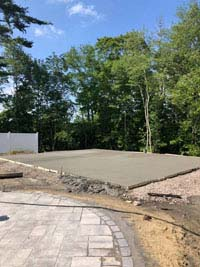 Freshly poured concrete base, waiting to dry, for what will become a blue and gray residential basketball court in Easton, MA.