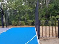 Highlighting right side and fance of blue and gray residential basketball court in Easton, MA.
