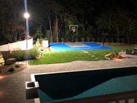 Blue and grey residential basketball court with custom Maximus logo under lighting in Walpole, MA.